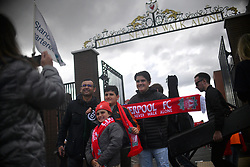 Liverpool fans pose for a photo outside the ground