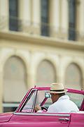 Man driving classic car on old town street, Havana, Cuba