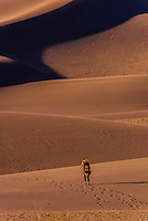 Sandboarder walking up dunes, Great Sand Dunes National Park and Preserve, near Mosca, Colorado USA. The park contains the tallest sand dunes in North America, rising about 750 feet above the floor of the San Luis Valley.