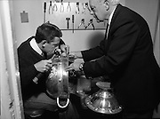Replica Of Sam Maguire Cup Assayed.  (R85)..1988..18.08.1988..08.18.1988..18th August 1988..The Sam Maguire Cup which was first won by 1928 All Ireland Champions, Kildare is being replaced by a replica for the 1988 final. The original cup was wrought by Hopkins and Hopkins of Dublin to the design of the Ardagh Chalice and is made of silver..The replica has been made by Kilkenny based silversmith Mr Desmond Byrne. the silver for the replica wa presented to the GAA by Mr Kieran Eustace, Managing Director, Johnson Matthey, Grafton Street, Dublin. The replica is hand crafted to match the eacct design and dimensions of the original. Today in Dublin Castle the new 'Sam Maguire' was stamped with the Millennium Stamp by the Assay Master, Dublin Castle...Picture shows Mr Gerry Smyth (L),Marking Room Manager,Assay Office,Dublin stamping the cup with the Millennium Stamp. He is being assisted by Mr Ronnie LeBas,former Assay Master of the Goldsmiths Co, Dublin Castle.