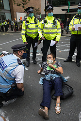 Metropolitan Police officers ask an activist from HS2 Rebellion, an umbrella campaign group comprising longstanding campaigners against the HS2 high-speed rail link as well as Extinction Rebellion activists, to leave the road outside the Department for Transport during a protest on 4 September 2020 in London, United Kingdom. Activists glued themselves to the doors and pavement outside the building and sprayed fake blood around the entrance during a protest which coincided with an announcement by HS2 Ltd that construction of the controversial £106bn high-speed rail link will now commence.