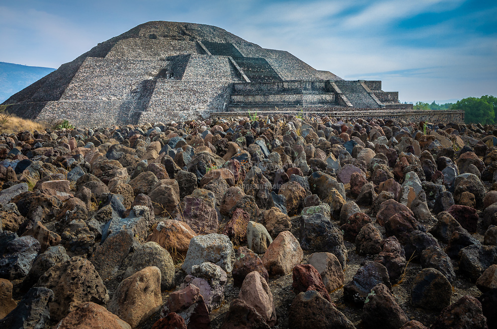 """The Pyramid of the Moon is the second largest pyramid in modern-day San Juan Teotihuacán, Mexico, after the Pyramid of the Sun. It is located in the western part of the ancient city of Teotihuacan and mimics the contours of the mountain Cerro Gordo, just north of the site. Some have called it Tenan, which in Nahuatl, means """"mother or protective stone."""" The Pyramid of the Moon covers a structure older than the Pyramid of the Sun. The structure existed prior to 200 AD.<br /> <br /> The Pyramid's construction between 200 and 250 AD completed the bilateral symmetry of the temple complex. A slope in front of the staircase gives access to the Avenue of the Dead, a platform atop the pyramid was used to conduct ceremonies in honor of the Great Goddess of Teotihuacan, the goddess of water, fertility, the earth, and even creation itself. This platform and the sculpture found at the pyramid's bottom are thus dedicated to The Great Goddess.<br /> <br /> Opposite the Great Goddess's altar is the Plaza of the Moon. The Plaza contains a central altar and an original construction with internal divisions, consisting of four rectangular and diagonal bodies that formed what is known as the """"Teotihuacan Cross."""""""