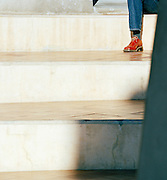 Detail of a person sitting on steps at dusk in Barcelona, Spain
