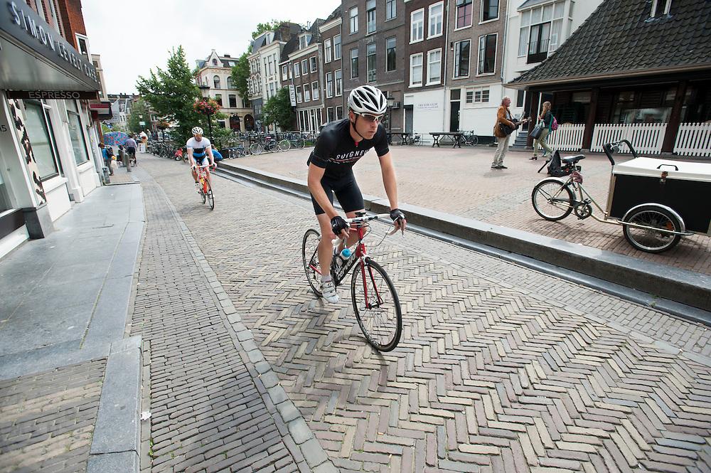 In Utrecht rijden twee mannen op een racefiets door de binnenstad.<br /> <br /> In Utrecht two men are riding on a road bike.