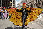 New York, NY - 25 June 2017. New York City Heritage of Pride March filled Fifth Avenue for hours with groups from the LGBT community and it's supporters. A man in a black body suit and with a yellow cape with red stars.