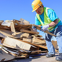 Paul Bobelu stacks cardboard to be recycled at Empowerment Inc. in Gallup Monday.