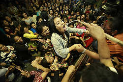 September 17, 2016 - Kathmandu, Nepal - A Nepalese girl climbs on top of others to drink local homemade alcohol from the mouth of idol Swet Bhairab on the fifth-day of the eight-day long Indrajatra festival, celebrated to honor Deity Indra, the King of Heaven and Lord of Rains at Basantapur Durbar Square in Kathmandu, Nepal on Saturday, September 17, 2016. Indrajatra is the biggest religious street festival held annually in Nepal. Singing, mask dance, rejoicing chariot processions and devotees offering prayers along with other rituals hold the eight-day festival celebrated by both Hindus and Buddhists. (Credit Image: © Skanda Gautam via ZUMA Wire)