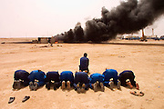 """Firefighters from the Kuwait Oil Company (called KWWK: Kuwait Wild Well Killers) pray at noon by the first oil well fire they were working on in Iraq's Rumaila Oil Field. Later in the day they extinguished this smoky fire and the next day stopped the flow of gas and oil with drilling mud using what is called a """"stinger"""", a tapered pipe on the end of a long steel boom controlled by a bulldozer. Drilling mud, under high pressure, is pumped through the stinger into the well, stopping the flow of oil and gas. The Rumaila field is one of Iraq's biggest with 5 billion barrels in reserve. The burning wells in the Rumaila Field were ignited by retreating Iraqi troops when the US and UK invasion began in March 2003. Rumaila is also spelled Rumeilah."""