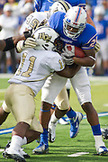 Dec 1, 2012; Tulsa, Ok, USA; UTulsa Hurricanes tailback Ja'Terian Douglas (25) is brought down by niversity of Central Florida Knights linebacker Jonathan Davis (11) and defensive lineman Cam Henderson (49) during a game at Skelly Field at H.A. Chapman Stadium. Tulsa defeated UCF 33-27 in overtime to win the CUSA Championship. Mandatory Credit: Beth Hall-USA TODAY Sports