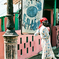 Hotel Jacmel sign, with local woman pose for photo.