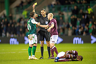 Stevie Mallan (#14) of Hibernian FC is booked by referee Kevin Clancy after fouling Arnaud Djoum (#10) of Heart of Midlothian during the Ladbrokes Scottish Premiership match between Hibernian FC and Heart of Midlothian FC at Easter Road Stadium, Edinburgh, Scotland on 29 December 2018.