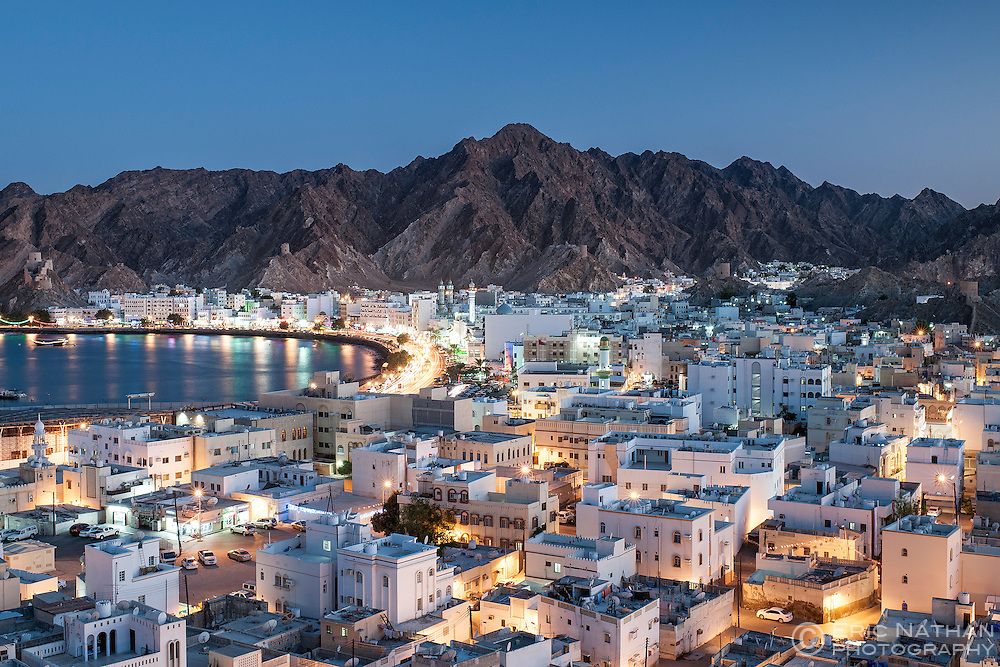 Dusk view of the district of Mutrah and surrounding mountains in Muscat, the capital of the Sultanate of Oman.