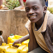 A young boy fills jerrycans with safe water at a small, protected spring in Nyankenke, Kisaro Sector, Rulindo District, Rwanda.