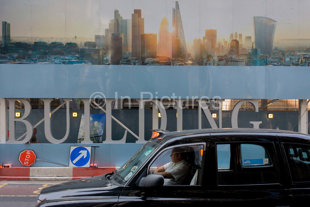 A black cab passes a large construction hoarding in the City of London, the  Square Mile, the capital's historic financial district. The illustration is located beneath a future office development of the Leadenhall Building by the Brookfield Multiplex construction company at 100 Bishopsgate in the financial district City of London. 100 Bishopsgate is a 40-storey commercial development, offering highly efficient and flexible floor space to meet the current and future demands of financial, insurance and legal occupiers. Located in the heart of the City of London, the development is in close proximity to Bank and Liverpool Street station commuter hubs.