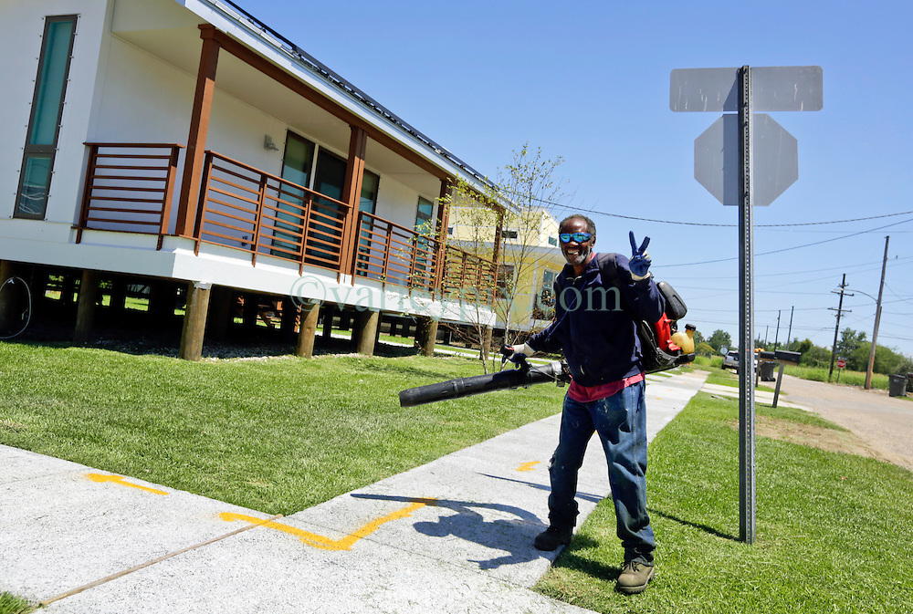 26 August 2015. New Orleans, Louisiana. <br /> Hurricane Katrina revisited. <br /> Rebuilding the Lower 9th Ward. <br /> A lawn maintenance man with his air blower and 'Make it Right' houses inspired by actor Brad Pitt continue to provide hope for the rebirth of the community following the devastation of hurricane Katrina a decade earlier.<br /> Photo credit©; Charlie Varley/varleypix.com.