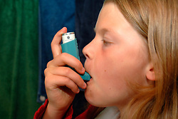 girl using her asthma pump