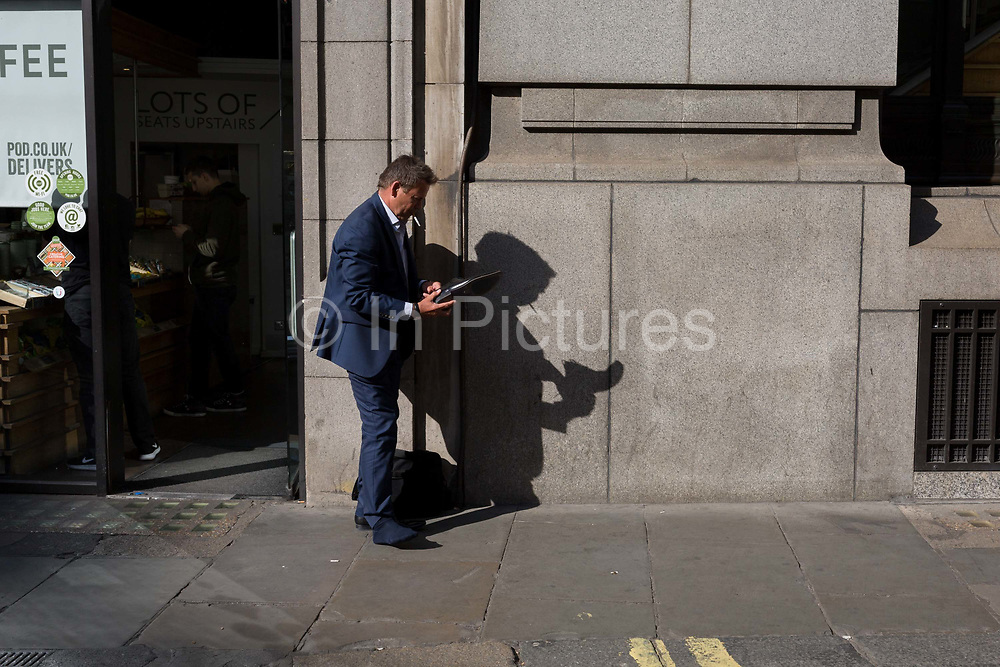 While smoking a cigarette, a businessman removes something uncomfortable from his shoe on Lombard Street, on 10th May 2017, in the City of London, England.