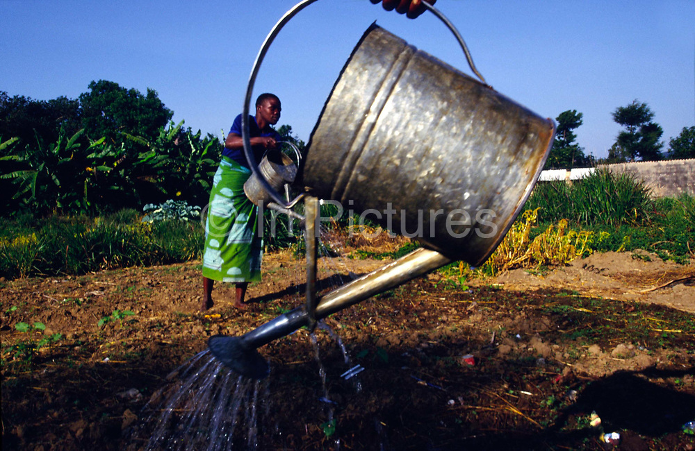 """Orphans watering the gardens in Shalom House an orphanage built by Marguerite Barankitse (known as the 'Angel of Burundi') in 1994. During the genocide, Barankitse, at great personal risk, managed to save 25 orphans, Hutu, Tutsi and Twa and built a home for them. Currently, she has helped more than 10,000 orphans and separated children who can grow up in an """"extended adopted family"""" in security, education and love."""