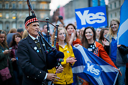 © Licensed to London News Pictures. 16/09/2014. Glasgow, UK. A Scottish Piper entertaining Yes voters and campaigners who hold a mass meeting at George's Square in Glasgow city centre on the evening of Tuesday, 16 September, two days ahead of the Scottish independence referendum. Photo credit : Tolga Akmen/LNP