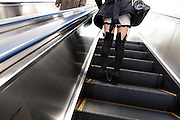 girl wearing hotpants going up the escalator with elderly man crossing on the other side