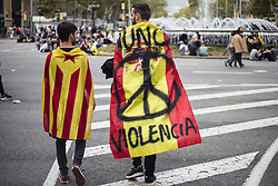 October 3, 2017 - Barcelona, Spain - Man waling with a Spanish flag with the motto ''Never violence'' walking with a other man with a catalan independentist flag during the protests and demonstrations in Barcelona during the general strike to condemn the Spanish Guardia Civil police violence to stop the Referendum of 1st of October, in Barcelona on October 3 of 2017. (Credit Image: © Xavier Bonilla/NurPhoto via ZUMA Press)