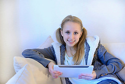 Teenage girl using digital tablet on couch, smiling