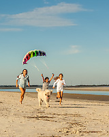 Three siblings, two sisters and their brother, run down the beach with a colorful kite in the sky above them. Their dog runs along with them.