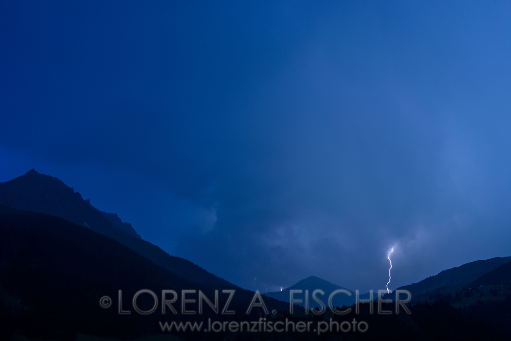 Thunderstorm with lightnings over the Oberhalbsteiner Alps the Piz Arblatsch and Mez viewed from Savognin at dusk, Parc Ela, Grisons, Switzerland
