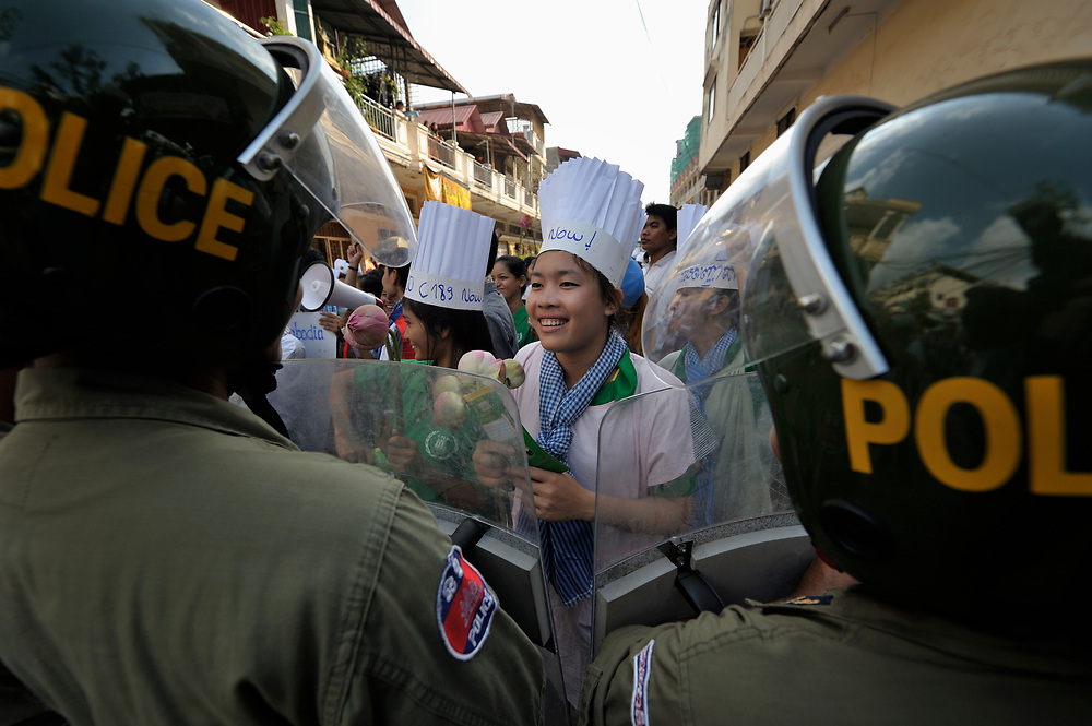 A woman protester talks with a police officer as informal sector workers, including domestic workers and tuk-tuk drivers, attempt to protest in Phnom Penh on December 10, 2012. Observing International Human Rights Day, they were calling for the Cambodian government to ratify ILO Convention 189 guaranteeing the rights of domestic workers, and planned to take their request to the prime minister's office, but police stopped them far short of their goal.