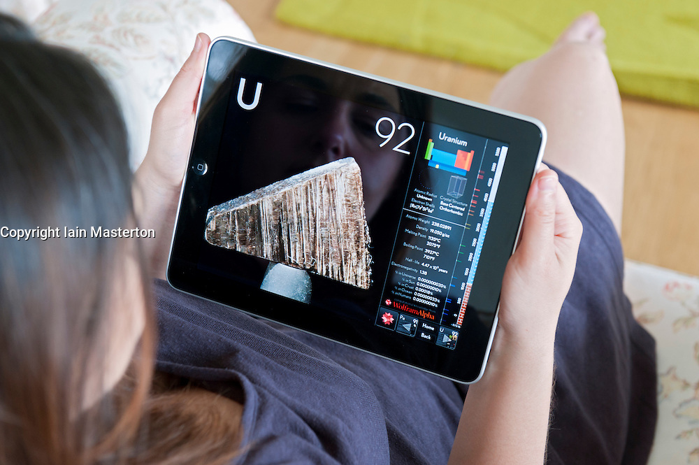 Woman using an interactive science app of Periodic Table of the Elements on an iPad digital tablet