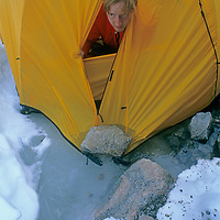 A mountaineer looks out with surprise at a sudden meltwater stream that has suddenly started flowing under his tent on Canada's Baffin Island.