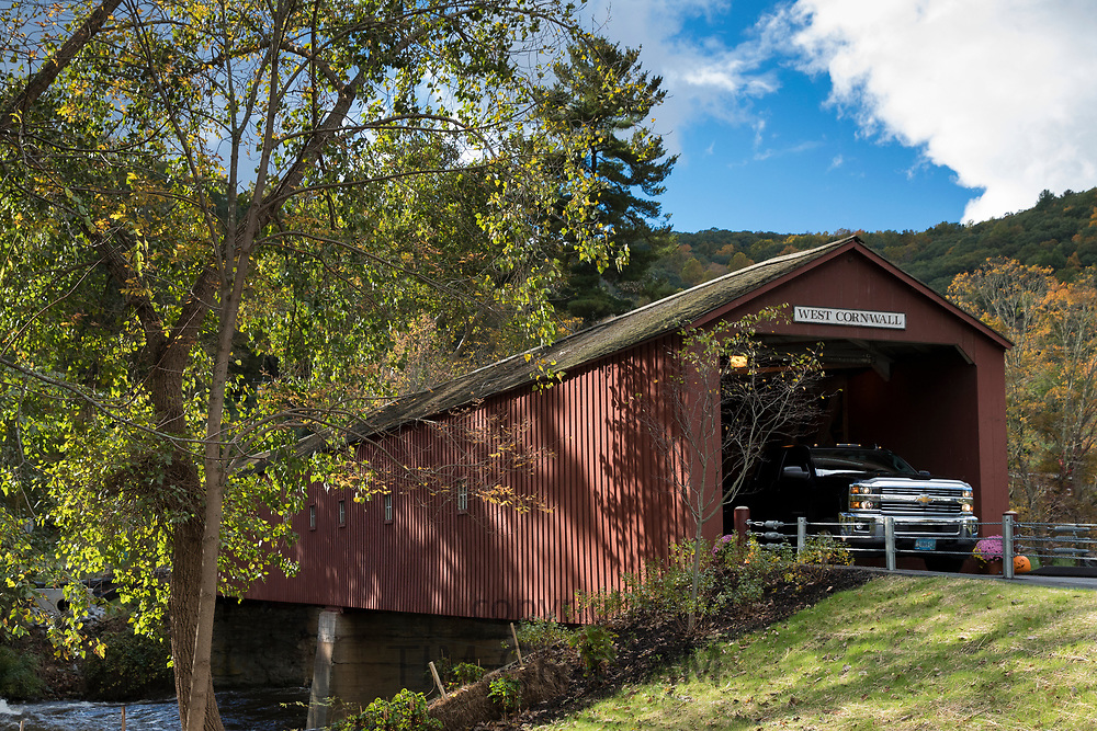 Automobile drives through West Cornwall covered bridge over Housatonic River during The Fall in Connecticut, USA