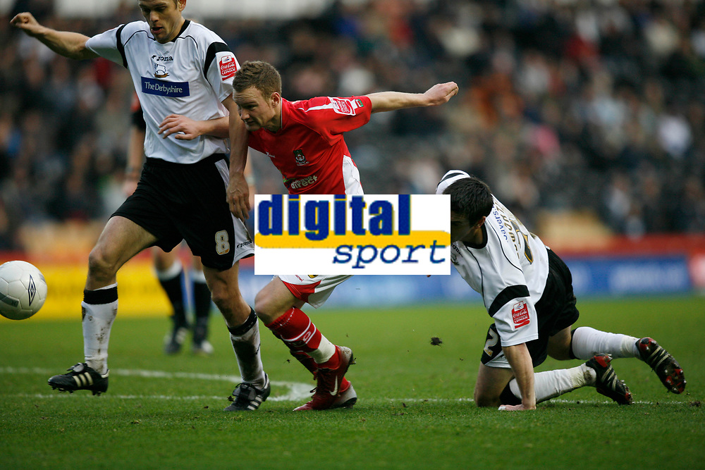 Wrexham's Matty Done (red) tries to break therough the Derby County defence
