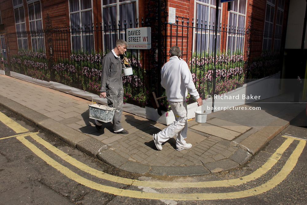 Two decorators walk past the construction hoarding belonging to Claridges in Mayfair, Westminster.