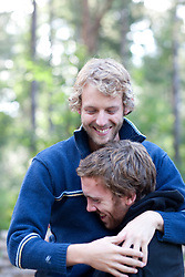Close up of two young men hugging and smiling