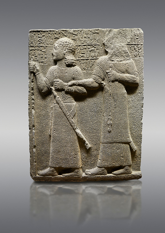 """Picture & image of Hittite monumental relief sculpted orthostat stone panel of Royal Buttress. Basalt, Karkamıs, (Kargamıs), Carchemish (Karkemish), 900-700 B.C. Anatolian Civilisations Museum, Ankara, Turkey.<br /> <br /> King Araras holds his son Kamanis from the wrist. King carries a sceptre in his hand and a sword at his waist while the prince leans on a stick and carries a sword on his shoulder. <br /> <br /> Hieroglyphs reads; """"This is Kamanis and his siblings. I held his hand and despite the fact that he is a child, I located him on the temple. This is Yariris' image"""".  <br /> <br /> Against a gray background. .<br />  <br /> If you prefer to buy from our ALAMY STOCK LIBRARY page at https://www.alamy.com/portfolio/paul-williams-funkystock/hittite-art-antiquities.html  - Type  Karkamıs in LOWER SEARCH WITHIN GALLERY box. Refine search by adding background colour, place, museum etc.<br /> <br /> Visit our HITTITE PHOTO COLLECTIONS for more photos to download or buy as wall art prints https://funkystock.photoshelter.com/gallery-collection/The-Hittites-Art-Artefacts-Antiquities-Historic-Sites-Pictures-Images-of/C0000NUBSMhSc3Oo"""