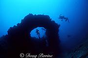 divers investigate puka (hole) in lava ledge, south shore, Kauai, Hawaii ( Pacific )