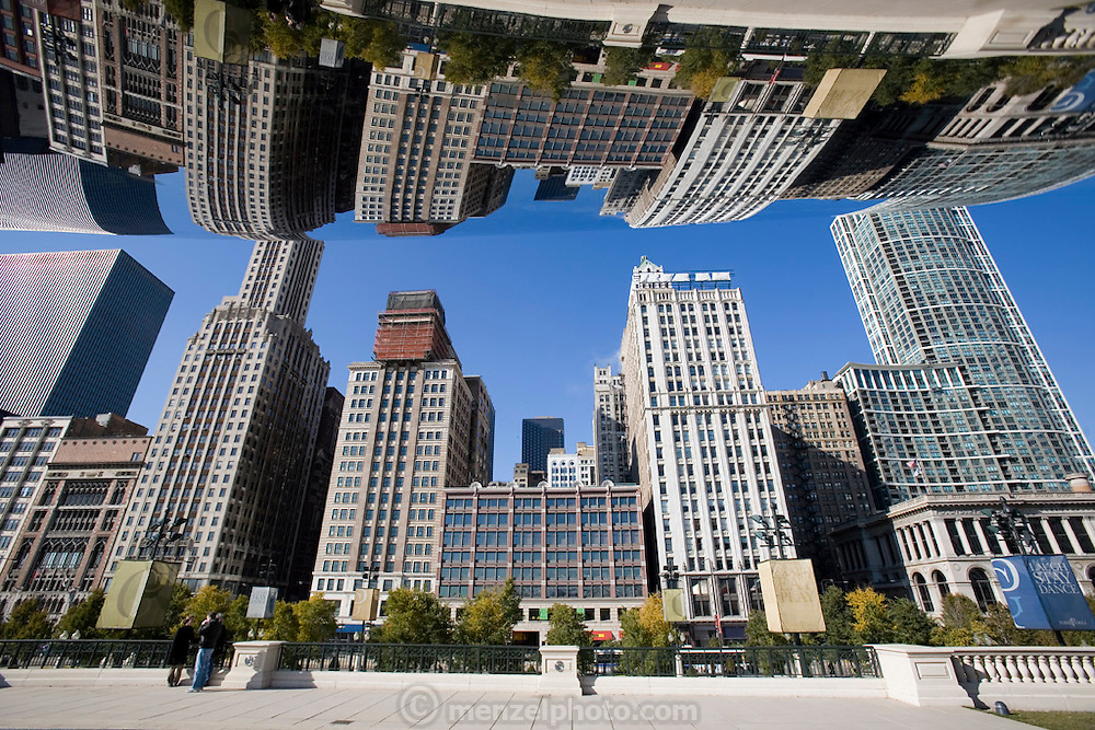 A large mirroring metal sculpture called The Cloud Gate, at Millennium Park, Chicago, Il, bends the downtown cityscape. USA. By British artist Anish Kapoor.