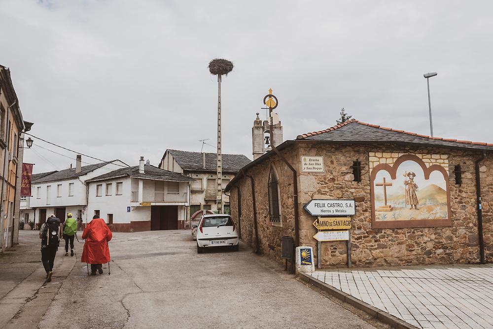 Pilgrims walking the Camino de Santiago pass through the town of Columbrianos, near Ponferrada. (July 2, 2018)