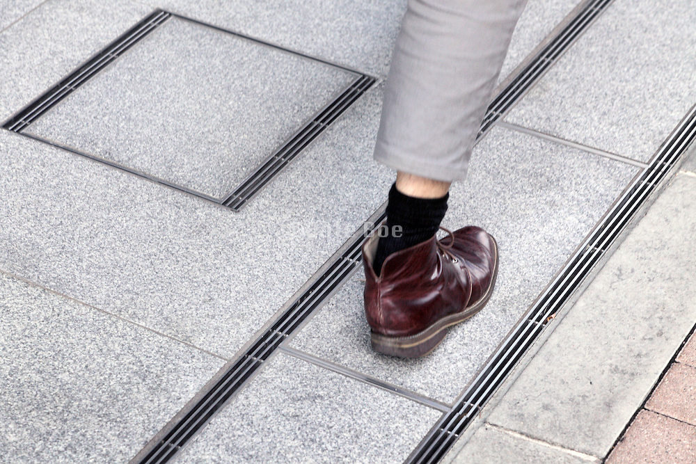 shoe and foot of a male person walking on the pedestrian pavement