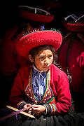 Local girl in traditional dress weaving at Chinchero Town Sunday Market, Cusco Region, Peru, South America
