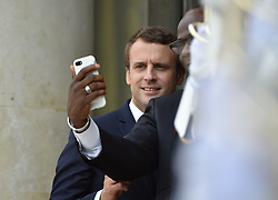 French President Emmanuel Macron, left, poses for a selfie with unidentified member of the delegation after he accompanies Ivory Coast's President Alassane Ouattara at the end of their meting at the Elysee Palace in Paris, France, Sunday, June 11, 2017, June 11, 2017. Photo by Christian Liewig/ABACAPRESS.COM    596213_001 Paris France