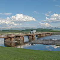 MONGOLIA.   Four-wheel drive van crosses bridge over Bagrakh River near Uulan Uul in southern Darhad Valley.  Horidal Saridag Mountains bkg.   This bridge washes out occasionally in floods.