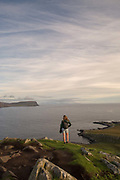 A woman overlooking Neist Point in Glendale on the 4th September 2016 on the Isle of Skye in Scotland in the United Kingdom. Neist Point is the most Westerly point on the Isle of Skye with views over Moonen Bay to Waterstein Head.