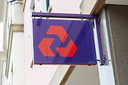 NatWest bank sign on wall outside branch, UK
