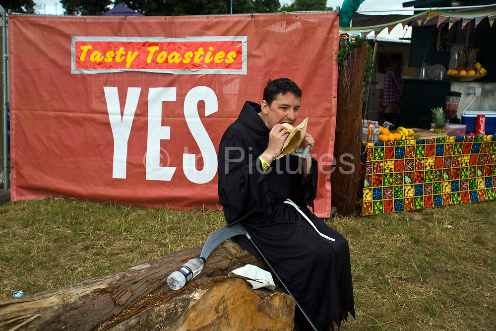 A man dressed as the Grim Reaper eats a sandwich on a log at the Standon Calling Festival in Hertfordshire, UK.<br /> Standon Calling is a small independent festival set among the hills in Herfordshire that showcases World Music, Indie Music and dance Music. It is one of the new, small and quirky boutique festivals which have become popular in the UK.