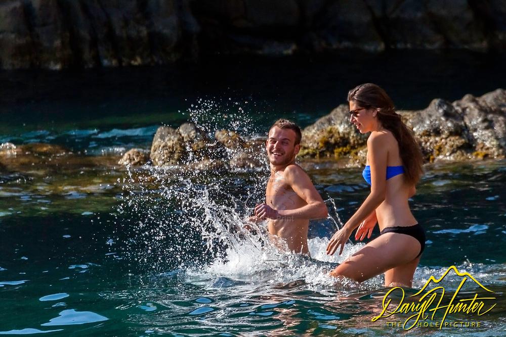A young couple head into the Riomaggiore Harbor at Cinque Terre Italy