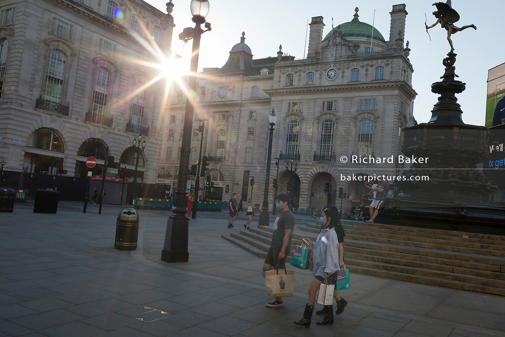 With a further 149 reported dying from Coronavirus in the last 24hrs, taking the UK death toll to 43,320, shoppers walk under the statue of Eros in Piccadilly Circus during the Covid pandemic, on 25th June 2020, in London, England.