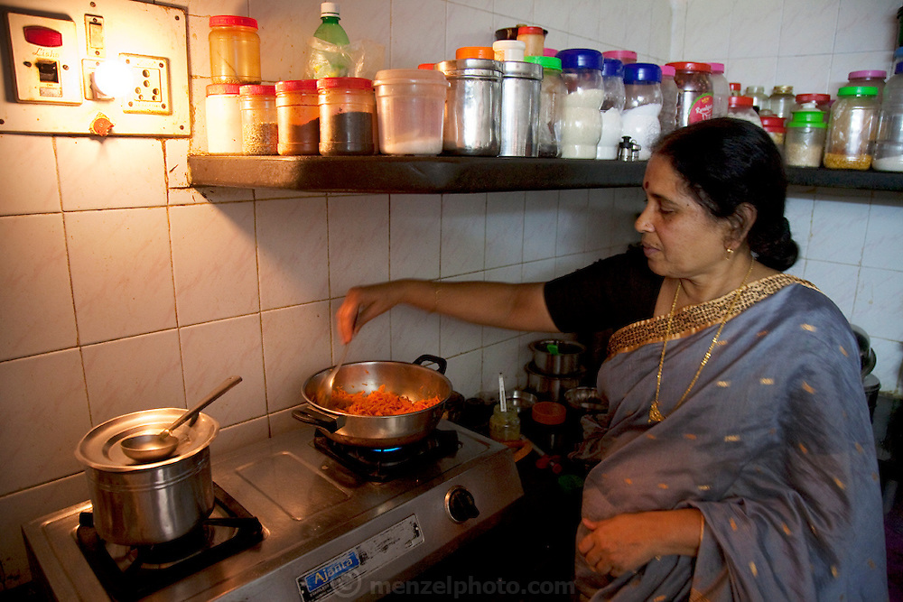 The mother of Shashi Kanth, a call center worker, prepares food in the small kitchen at the home she shares with her son in Bangalore, India. (Shashi Kanth is featured in the book What I Eat: Around the World in 80 Diets.) Shashi loves his mother's traditional southern Indian food at home, but when he's at work his dinner options are KFC and Beijing Bites, the fast-food restaurants on the ground floor of the high-rise where he works, located on the edge of Bangalore. Like many of his co-workers, Shashi relies on quick fast food meals, candy bars, and coffee, to sustain him through the long nights spent talking to westerners about various technical and billing problems. MODEL RELEASED.