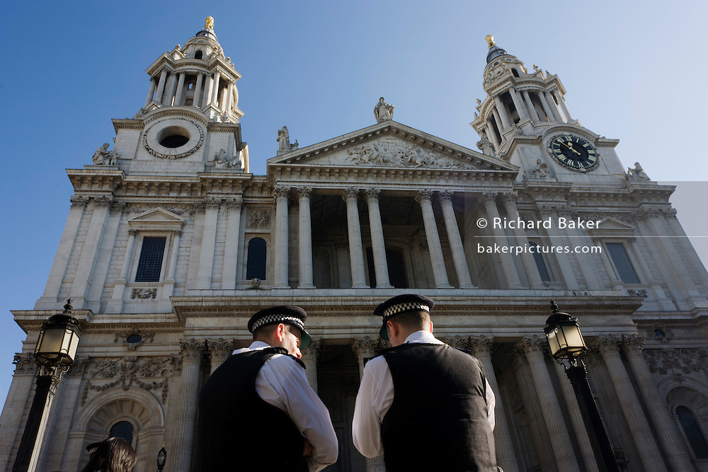 Metropolitan police officers stand beneath the pillars and belltowers of Sir Christopher Wren's St. Paul 's Cathedral in the City of London during world corporate greed and government austerity measures protests.